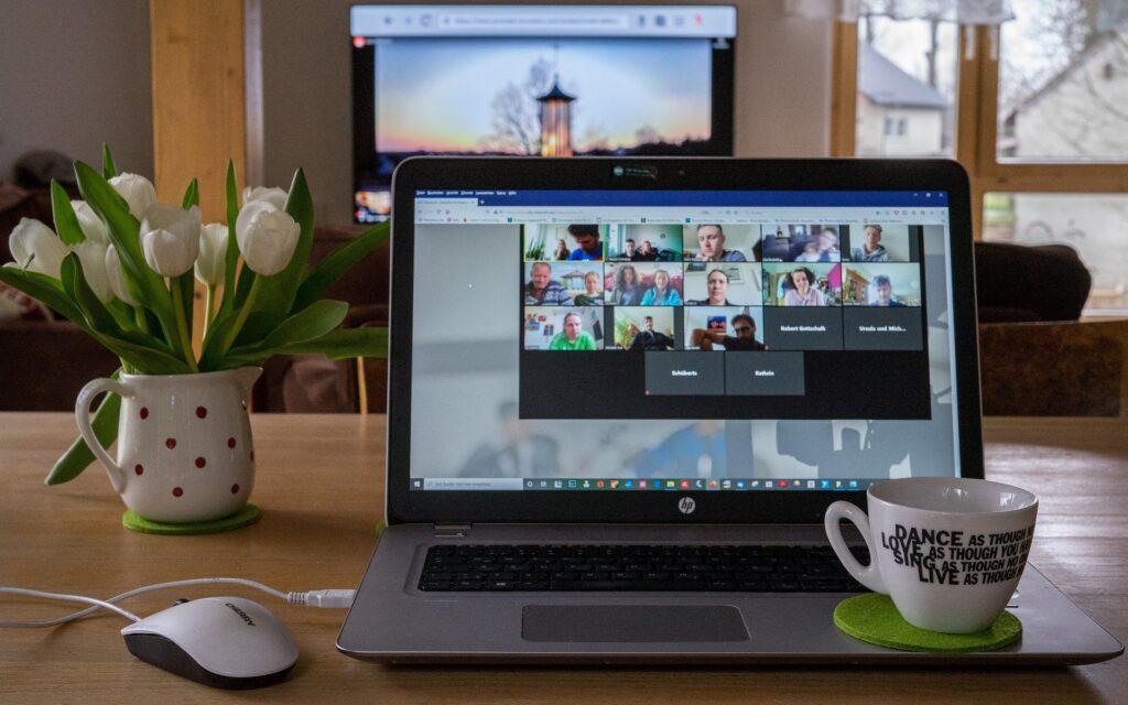 Geöffnetes Laptop zeigt ein Zoom-Meeting mit mehreren Leuten. Kaffeetasse steht rechts neben dem Touchpad. Dieses Bild unterstreicht unsere vielfältigen Online-Angebote.