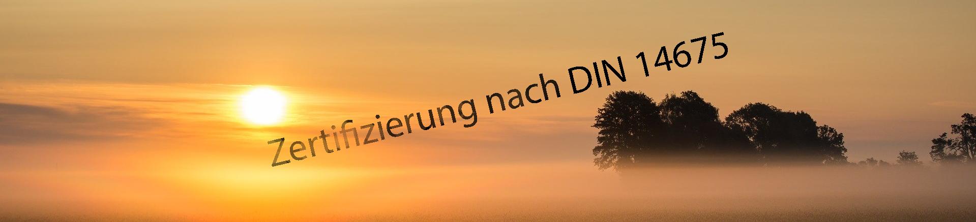 Nebelbid in orange-gelb. Hinter dem Dunst (Nebel) geht die Sonne unter. Aus dem Nebel taucht eine Schriftzug auf: Zertifizierung nach DIN 14675